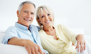 Smiling mature man with his wife sitting together on sofa